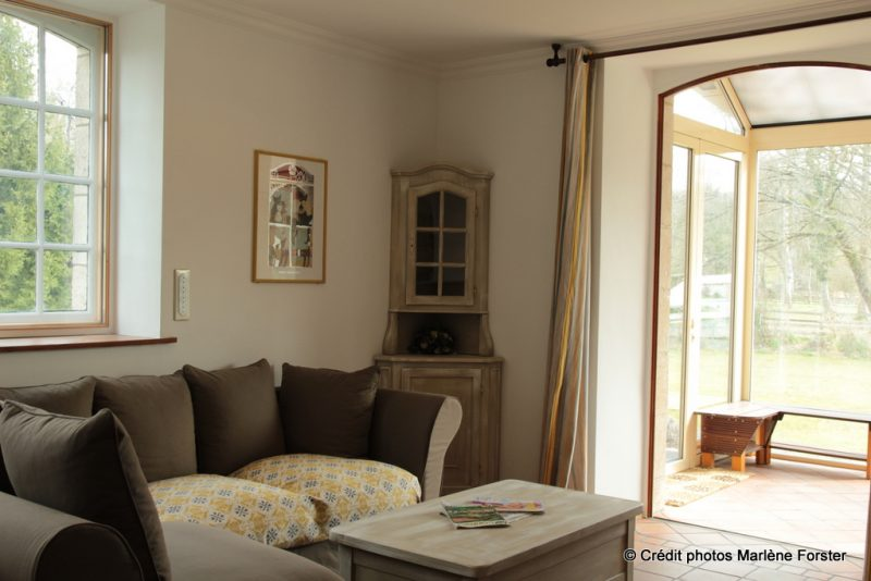 Coin Salon canapé vers véranda - Gîte Moulin - www.moulindescombes.com